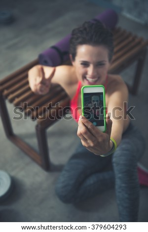 Body and mind workout in loft fitness studio. Closeup on smiling fitness woman sitting in loft gym and taking selfies - stock photo