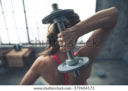 Body and mind workout in loft fitness studio. Seen from behind fitness woman lifting dumbbell - stock photo