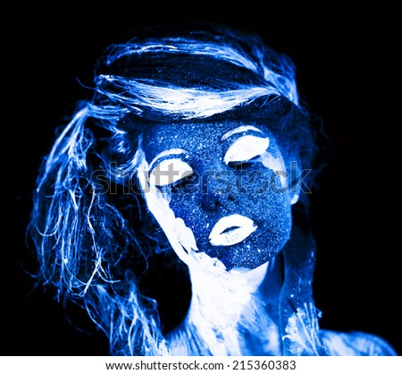 Body art glowing in ultraviolet light - stock photo