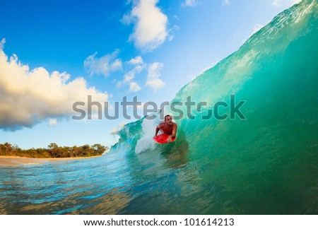 Body Boarder on Large Wave Surfing in the Tube Getting Barreled - stock photo