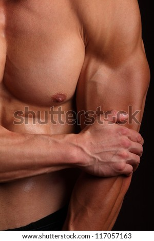 Body Builder flexing his biceps muscular build - stock photo