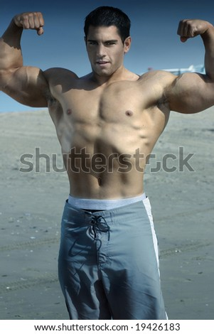 Body builder on beach flexing with blue toned light - stock photo