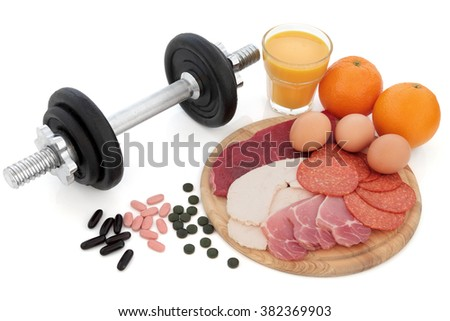Body building dumbbell weights with supplement tablets, high protein food of chicken, steak, bacon, eggs, oranges and glass of smoothie juice over white background. - stock photo