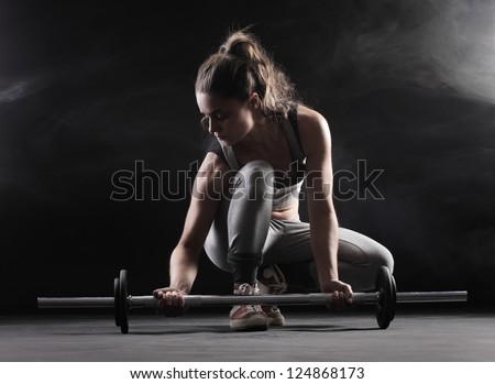 Body building: young woman lifting weights - stock photo