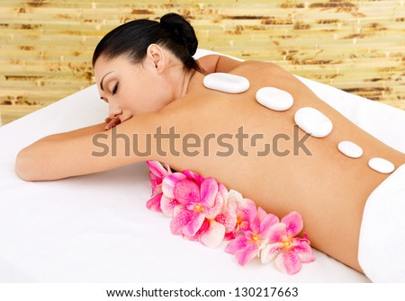 Body care for young woman at beauty spa salon. White hot stones on female back. - stock photo
