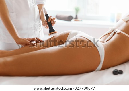 Body care. Spa treatment. Ultrasound cavitation body contouring treatment. Woman getting anti-cellulite and anti-fat therapy in beauty salon. - stock photo