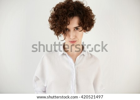 Body language. Headshot of student girl looking at the camera with displeased expression after failing exams at university. Isolated portrait of annoyed and sad young woman with short curly hair   - stock photo