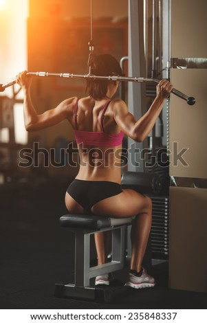 Body of a beautiful young girl in the fitness room rear view. Athletic young woman doing a fitness workout. Attractive fitness woman, trained female body, lifestyle portrait, caucasian model - stock photo