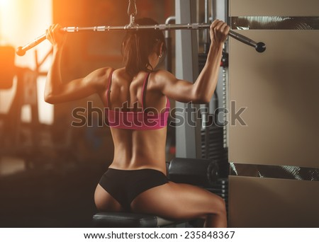body of a beautiful young girl in the fitness room rear view. Athletic young woman doing a fitness workout - stock photo