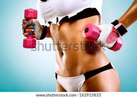 Body of a young fit woman lifting dumbbells - stock photo