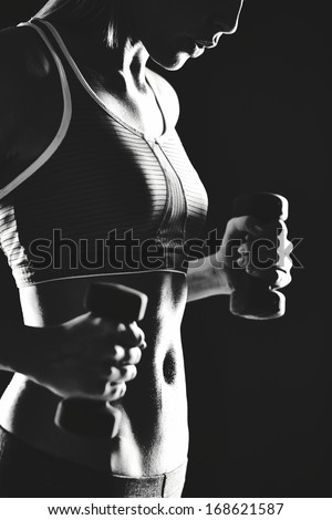 Body of slim female in activewear doing exercise with dumbbells - stock photo