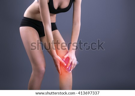 Body pain. Close up studio shot of woman. Woman suffering from knee pain. Red spot on knee. Woman holding freezing gel on knee - stock photo