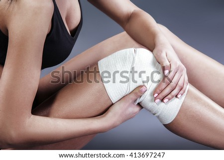 Body pain. Close up studio shot of woman. Woman suffering from knee pain. Woman with elastic bandage on knee - stock photo