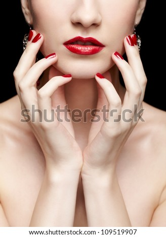 body part portrait of young beautiful brunette woman on black touching her face with manicured hands - stock photo