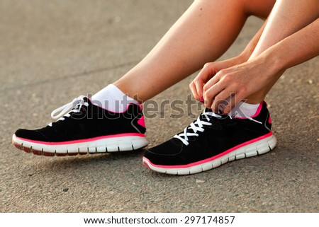 body parts of runner woman tying laces at sunset - stock photo
