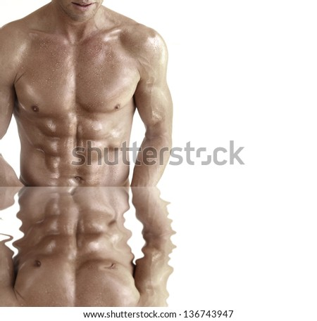 Body portrait of a muscular guy against white background with reflection - stock photo