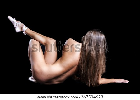 Body puzzle. A nude sexy lady dancer on black background - stock photo