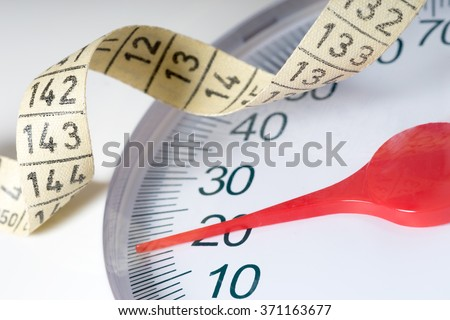 Body scale with a measuring tape / Body scale - stock photo