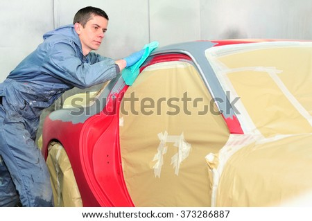Body worker preparing car surface for paint. - stock photo