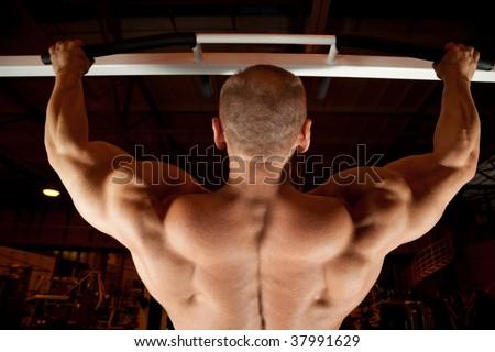 bodybuilder back pull-up in training room - stock photo