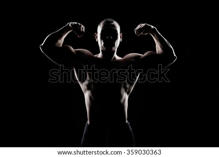 bodybuilder demonstrates biceps on a dark background - stock photo