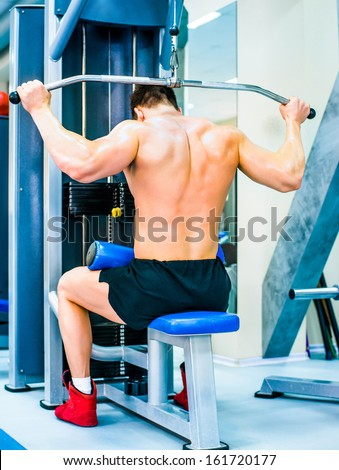 bodybuilder doing exercises on the simulator - stock photo