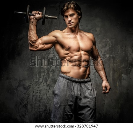 Bodybuilder doing shoulders exercises with dumbell over grey wall. - stock photo