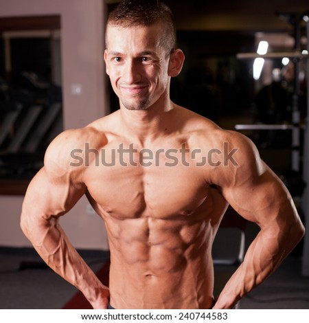 bodybuilder flexing his muscles in gym - stock photo