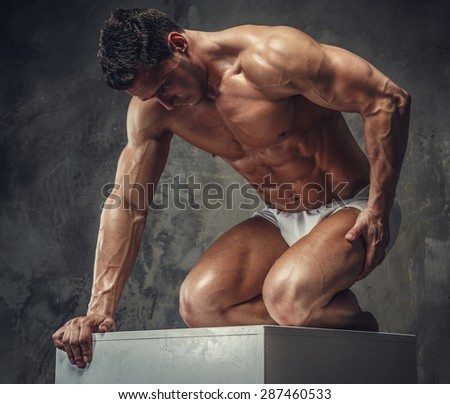 Bodybuilder guy posing on white podium on his knees. Isolated on grey background. - stock photo