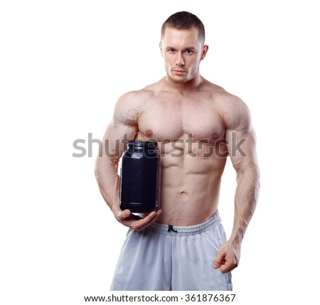 Bodybuilder holding a black plastic jar with whey protein isolated on white background - stock photo