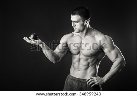 Bodybuilder holding a fruit on a dark background. Demonstration professional athlete healthy diet. Tasty and healthy, full of vitamins food. Photos for sporting and social magazines, posters. - stock photo