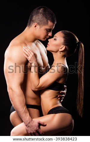 Bodybuilder holding fit girls' leg. Muscular athlete holds woman's leg. Stay close to me. Enjoy your time. - stock photo