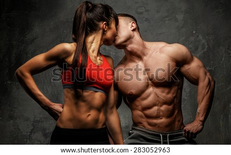 Bodybuilder kissing his fitness female - stock photo