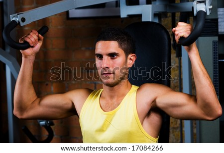 Bodybuilder male shoulders deltoids vest working out in gym on back machine - stock photo