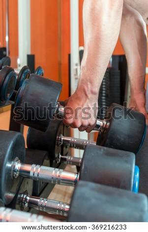bodybuilder man hand taking out heavy dumbbell in fitness center - stock photo