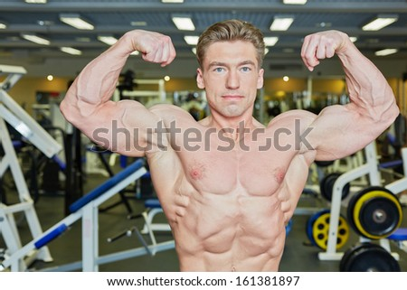Bodybuilder poses demonstrating tense muscles in gym hall - stock photo