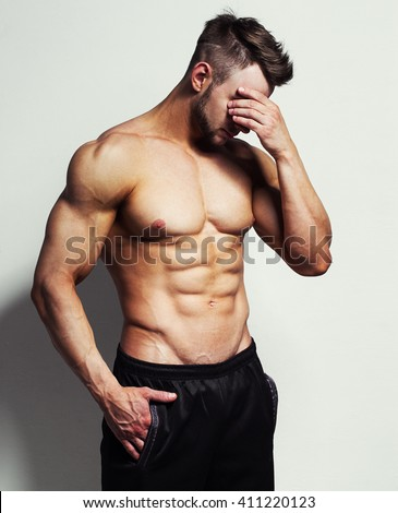 bodybuilder posing. Handsome power athletic guy male.  Sad, worried or unhappy young muscular man with hands on his head, isolated on white - stock photo