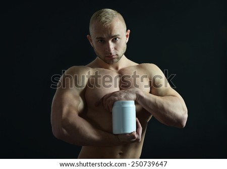 Bodybuilder posing his muscles on black background - stock photo