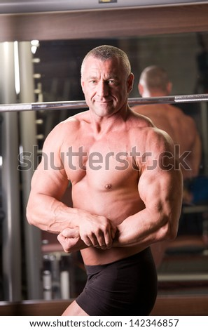 bodybuilder posing in a gym - stock photo