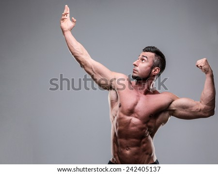 Bodybuilder posing over gray background - stock photo