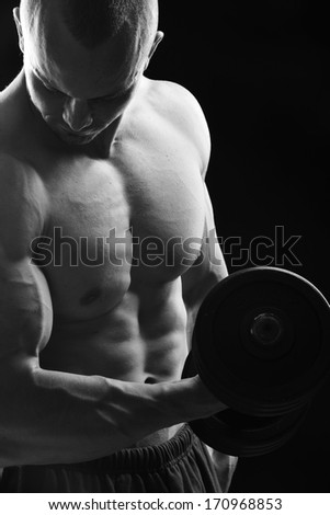 Bodybuilder posing with dumbbell - stock photo