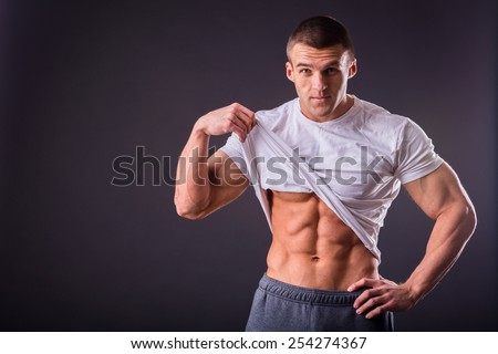 Bodybuilder showing his press. A man shows his abdominal muscles, raised his hand t-shirt. Press, muscles, show, bodybuilding. Sports guy. - stock photo