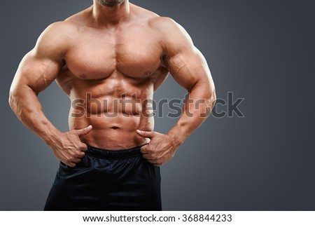 Bodybuilder showing ok sign to his perfect six pack abs. Midsection of shirtless man pointing at abs isolated on grey background with copy space - stock photo