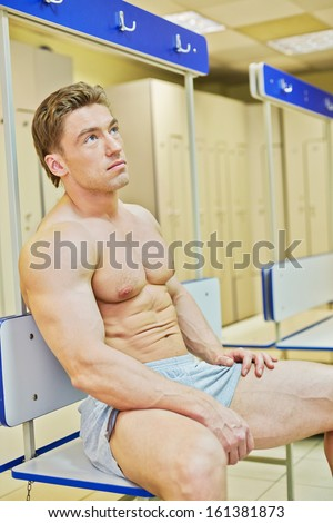 Bodybuilder sits tired leaning back on bench in locker room after finishing training - stock photo