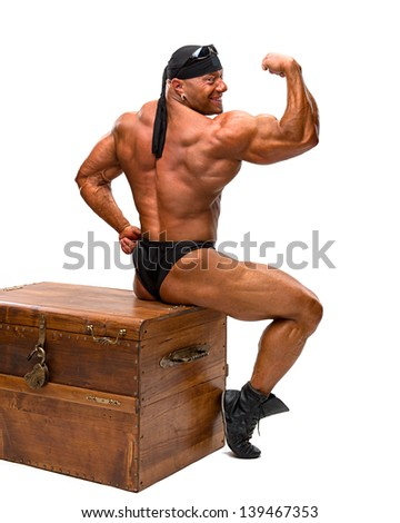 Bodybuilder sitting on a wooden chest on a white background - stock photo