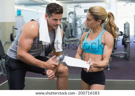 Bodybuilder talking with his personal trainer at the gym - stock photo