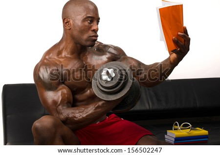 Bodybuilder training hard while reading a book. Strong man with perfect abs, pecs shoulders,biceps, triceps. Isolated on white background  - stock photo