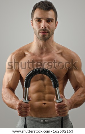 Bodybuilder training with a bendy bar. Strong man with perfect abs, pecs shoulders,biceps, triceps - stock photo