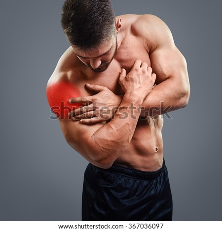 Bodybuilder with shoulder pain over gray background. Concept with highlighted glowing red spot. - stock photo