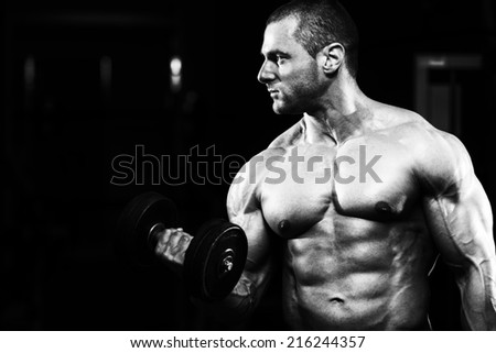 Bodybuilder Working Out Biceps - Dumbbell Concentration Curls - stock photo